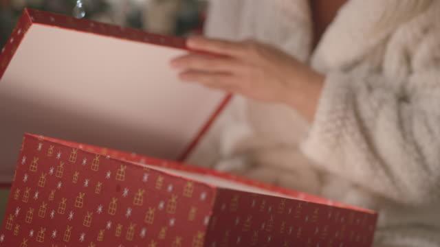 vídeos y material grabado en eventos de stock de cu mujer afectuosa divirtiéndose abriendo su regalo de navidad - regalo de navidad