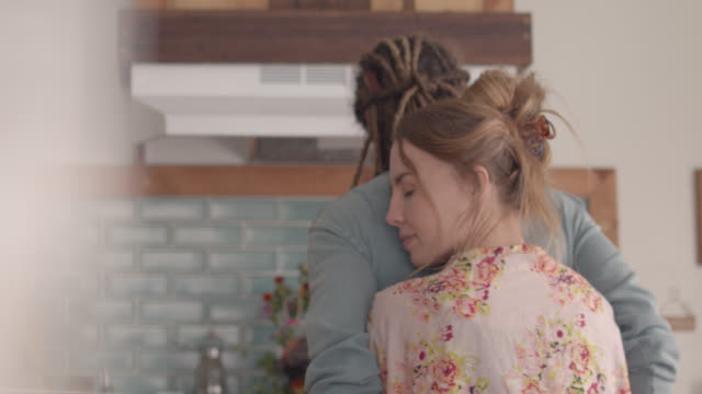 affectionate woman hugs young man from behind, talks to him in kitchen - vänskapsband bildbanksvideor och videomaterial från bakom kulisserna