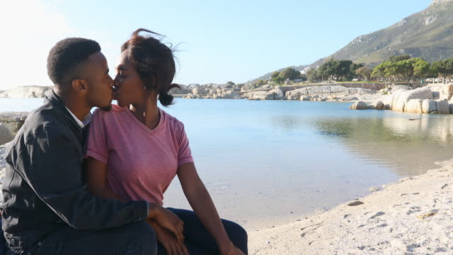 affectionate young african couple by the seaside - flirting stock videos & royalty-free footage