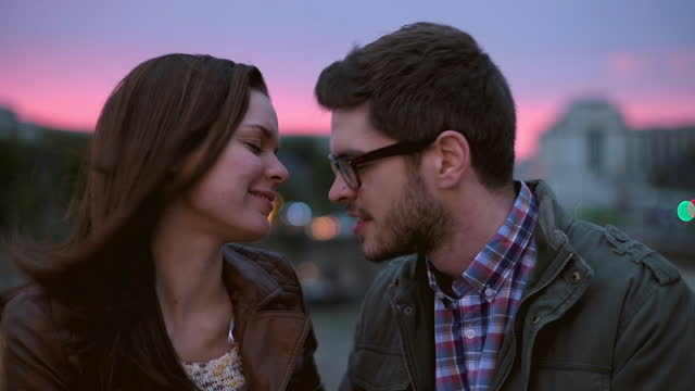 stockvideo's en b-roll-footage met affectionate young couple rub noses by the river seine at sunset on romantic night out in paris. - eskimokus geven
