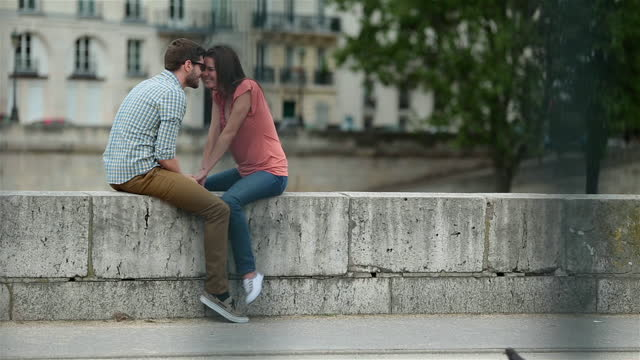 Affectionate young couple rub noses on a wall overlooking the Seine as pigeons fly past.