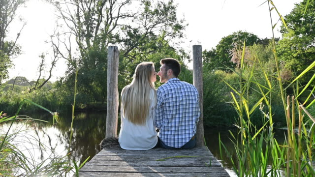 affectionate young couple sitting together on rural pier - reed grass family stock videos & royalty-free footage