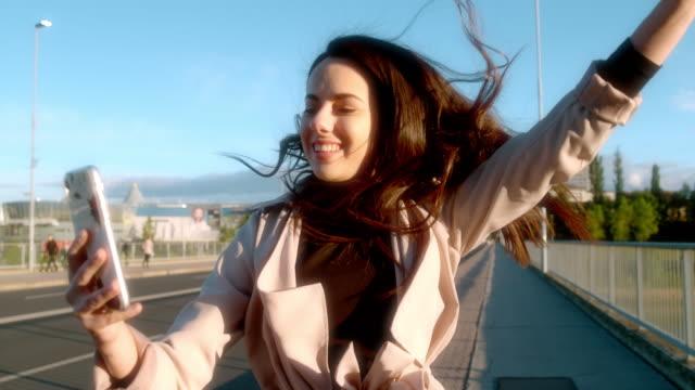slo mo giovane donna affettuosa che si fa selfie sul ponte - fashionable video stock e b–roll