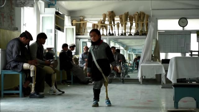Afghan amputees practice walking with their prosthetic limbs at the ICRC hospital for war victims in Kabul