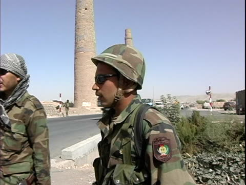 afghan and american soldiers patrolling busy street near minaret / afghanistan - basco video stock e b–roll