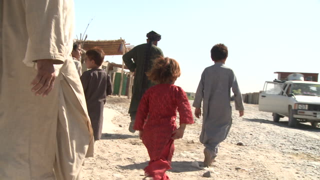 afghan children and their chaperones cross a dirt road. - afghanistan stock videos & royalty-free footage