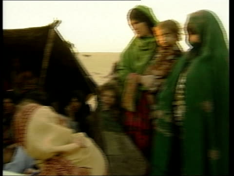vídeos de stock e filmes b-roll de afghan children crossing unguarded border into pakistan girls ducking under strands of barbed wire marking the border tents of refugees refugees camp... - kandahar