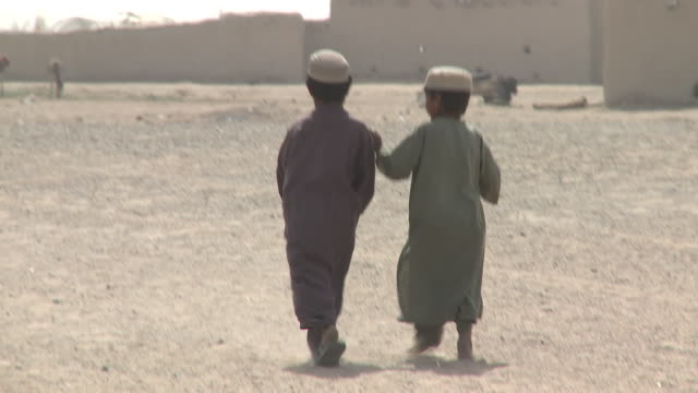 afghan children play soccer in a dusty field near a tent and stone buildings. - afghanistan stock videos & royalty-free footage