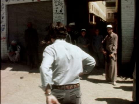 vidéos et rushes de john suchet in afghanistan; pakistan: peshawar: ext gv street in peshawar int men at table in hq photographs on wall tilt man two men at table ext... - afghanistan