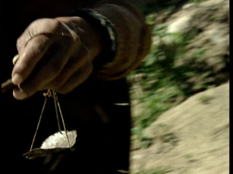 vidéos et rushes de afghan man checks balance of scales during sale of opium afghanistan - afghanistan