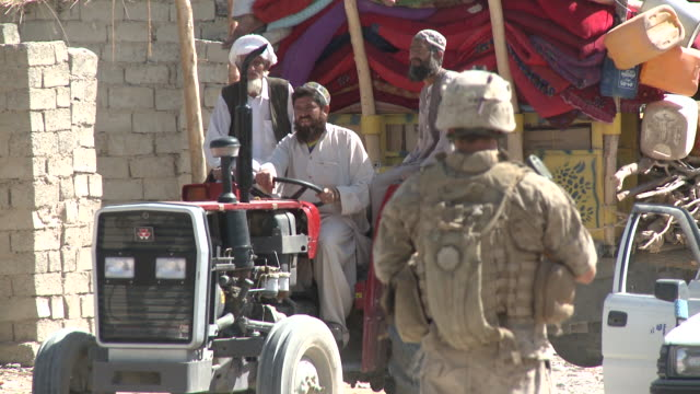 Afghan men drive a loaded tractor filled with goods.