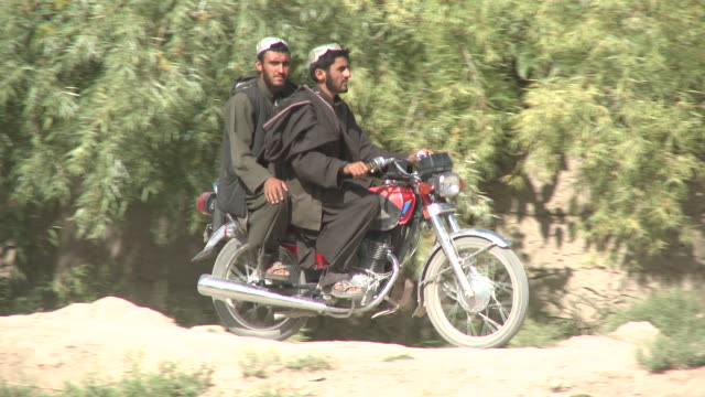 afghan men ride motorbikes on a bumpy dirt road. - bumpy stock videos & royalty-free footage