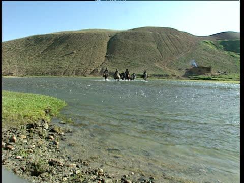 afghan men travel across shallow river on horseback in barren mountainous landscape afghanistan - landscape scenery点の映像素材/bロール