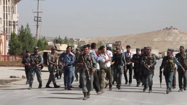 afghan police officers secure the road leading to a guest house where foreign contractors are reportedly staying after the taliban attacked the... - taliban stock videos & royalty-free footage