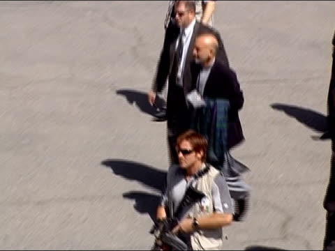 afghan president hamid karzai arriving at airport to fly to nato summit in istanbul / smiling and waving at people offscreen / kabul, afghanistan /... - 2004 stock videos & royalty-free footage