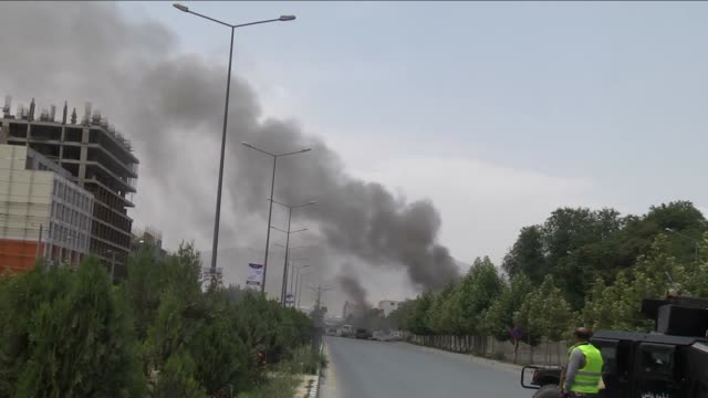 afghan security forces look on as black smoke billows from the afghan parliament building in kabul on june 22, 2015. taliban militants attacked the... - kabul stock videos & royalty-free footage