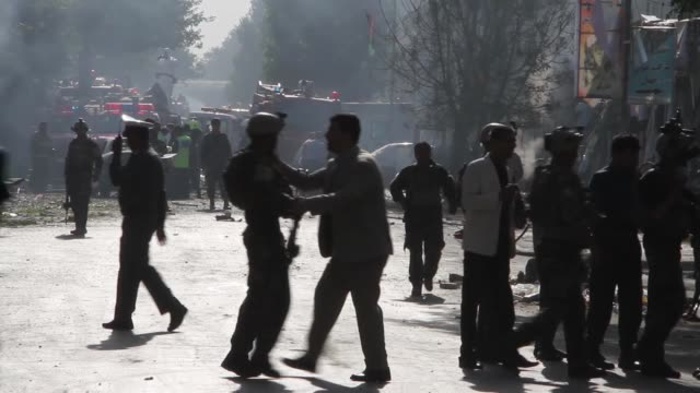 afghan security officials inspect the site of a suicide attack targeting a bus carrying employees of the ministry of petroleum and mines on july 24... - terrorism stock videos & royalty-free footage