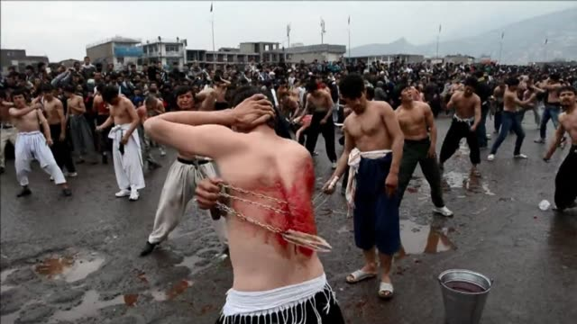 afghan shiite devotees beat themselves with chains and blades during commemorations to mark ashura in kabul - ashura muharram stock-videos und b-roll-filmmaterial