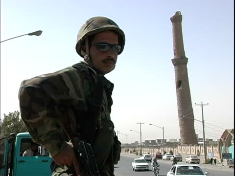 afghan soldier patrolling busy street near minaret / afghanistan - operazione enduring freedom video stock e b–roll