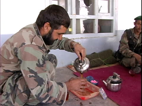 afghan soldier pouring tea for other soldiers / afghanistan - 注ぎ口点の映像素材/bロール