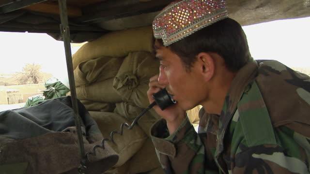stockvideo's en b-roll-footage met afghan soldier using telephone / musa qala, helmand province, afghanistan. - telefoonhoorn