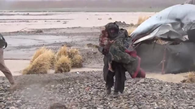 Afghan soldiers help residents in Afghanistan's Kandahar province evacuate as flash floods and heavy rains swept away homes and vehicles and...