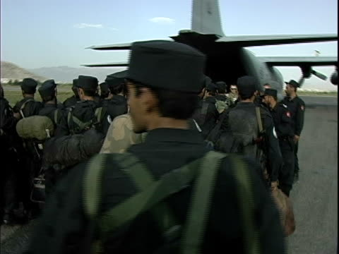 afghan soldiers waiting in line to board military airplane and carrying missiles in backpack / afghanistan - operazione enduring freedom video stock e b–roll