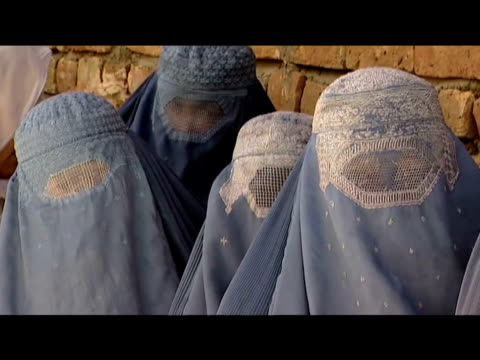 Afghan women dressed in burqas wait in line to place their votes in presidential elections Afghanistan 20 August 2009