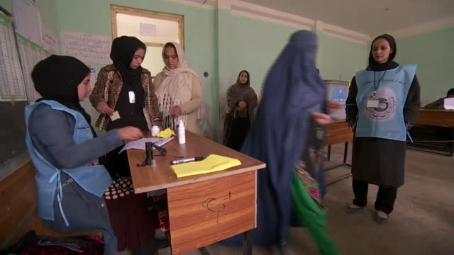 vidéos et rushes de afghan women queuing in polling station on election day to vote in presidential election - vêtement religieux