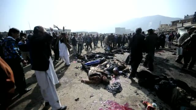 Afghan wounded men sit on the ground waiting for help at an explosion site in a religious ceremony in Kabul city centre on December 6 2011 Kabul...