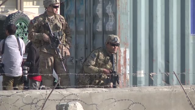 afghani and us security forces take security measures and investigate the crime scene where a car bombing staged against foreign personnel of a... - 武力攻撃点の映像素材/bロール
