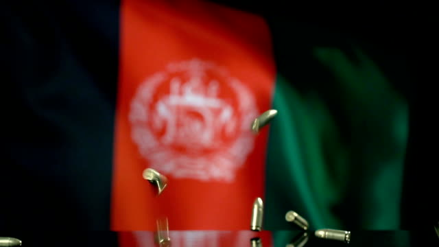 afghani flag behind bullets falling in slow motion - afghan national army stock videos & royalty-free footage