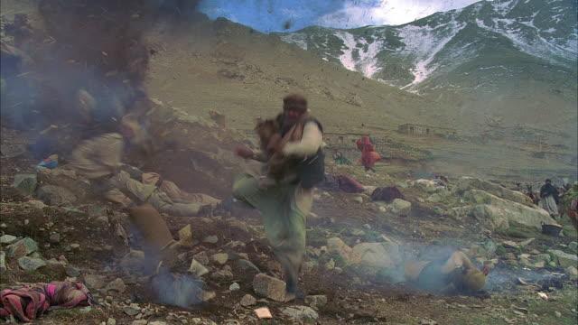 vídeos de stock e filmes b-roll de ws reenactment afghani refugees running from soviet gunfire/ morocco - refugiado