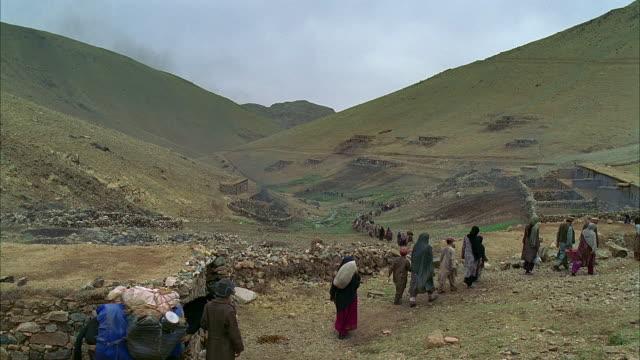 vidéos et rushes de ws reenactment afghani refugees walking at foot of a mountain/ morocco - réfugié