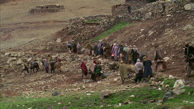 ha ws reenactment afghani refugees walking on hillside/ soviet artillery exploding and killing refugees/ morocco - aggression stock-videos und b-roll-filmmaterial