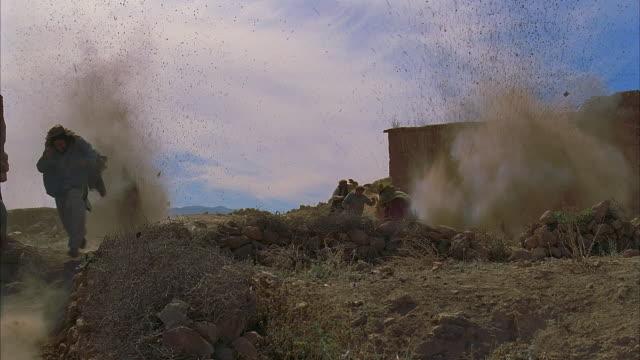 ws pan reenactment afghanis fleeing soviet gunfire and explosion/ morocco   - unknown gender stock videos & royalty-free footage