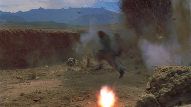 ws pan reenactment afghanis fleeing soviet gunfire/ woman holding baby getting shot and falling down/ morocco   - aggression stock-videos und b-roll-filmmaterial