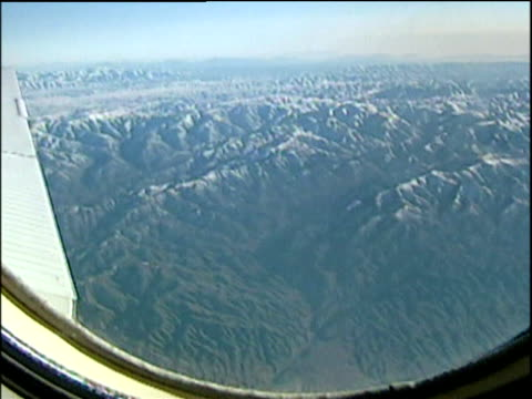 Afghanistan mountains through airplane window pan left to