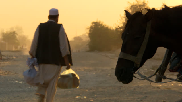 stockvideo's en b-roll-footage met afghanistan road with horse and people - afghanistan