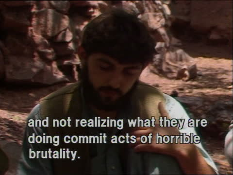 afghan guerrilla camp; tx:11.9.84/nat afghanistan: ext line of men kneeling, prayer mats in front of them, zoom in sergei dussov men bow faces to... - 起爆装置点の映像素材/bロール