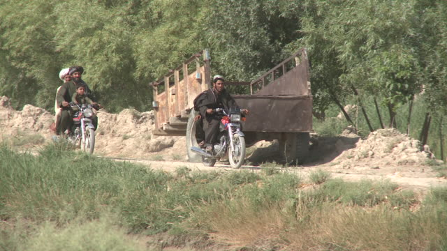 afghans use motorbikes to haul passengers on a bumpy dirt road. - bumpy stock videos & royalty-free footage