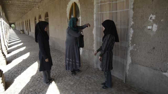 vidéos et rushes de afghans weavers decide on the type of weaving to do - châle