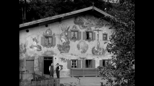 frame house w/ two men standing by doorway one in traditional bavarian alps hat fresco paintings on exterior wall of home farm family eating at table... - bavaria stock videos & royalty-free footage