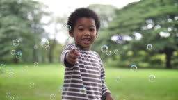 Africa boy playing bubble in public park