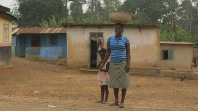 africa portrait of a mother carrying water on her head - village stock videos & royalty-free footage