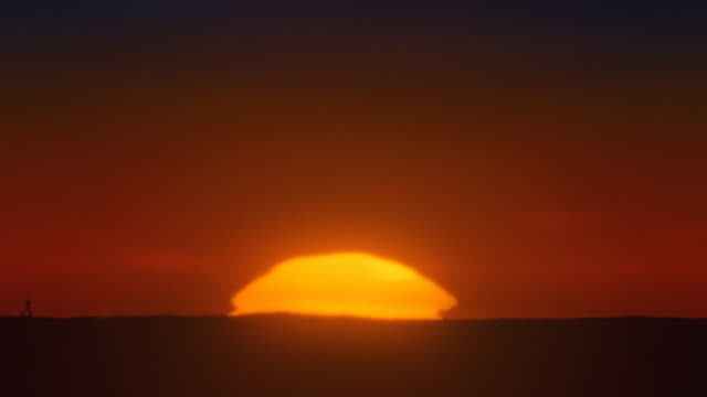 africa. timelapse african sunrise with big sun and inferior mirage - distorted stock videos and b-roll footage