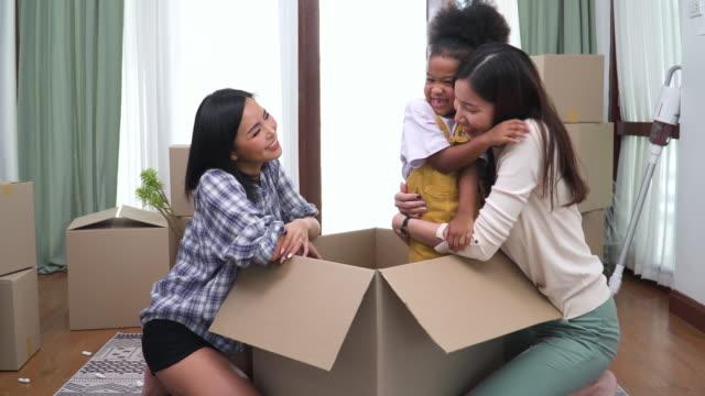 アフリカの養女は、紙箱の中から飛び降りて、移転日に新しい家で抱き合い、興奮した笑顔、幸せで若いアジアのlgbtq女性家族を驚かせました。同性愛のカップルと娘を持つ現代の家族は、� - 子供1人の家庭点の映像素材/bロール