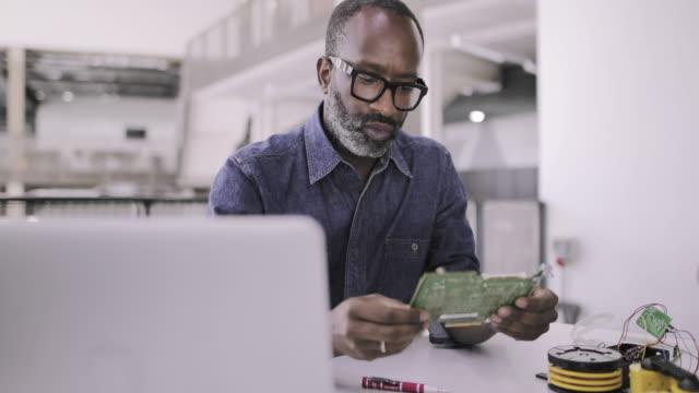 african american adult male working on robotics - schaltkreis stock-videos und b-roll-filmmaterial