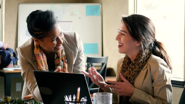 african american and caucasian businesswomen discuss something while looking at a laptop - assistant stock videos and b-roll footage