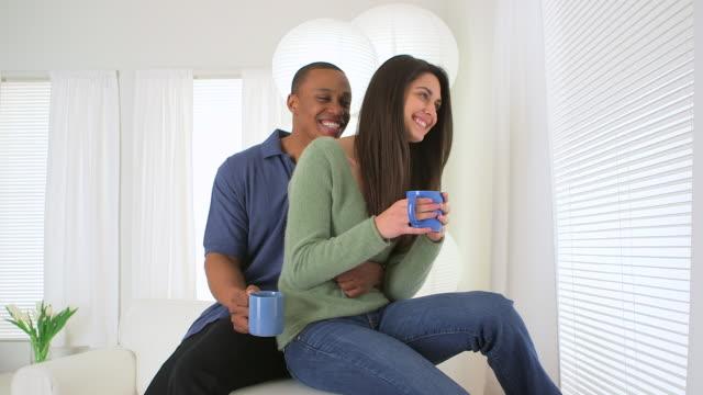 vídeos de stock e filmes b-roll de african american and caucasian couple drinking coffee together - fotografia de três quartos